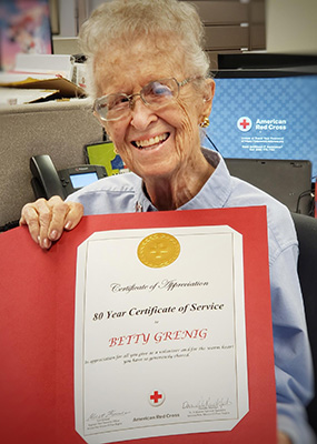 Betty smiles with her service award certificate.