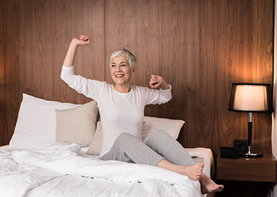 Senior woman waking up in bed stretching her arms out.
