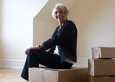 Senior woman sitting on packed up boxes.