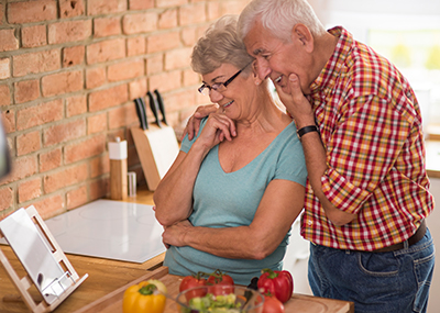 Older couple looking up recipes on an iPad in their kitchen.