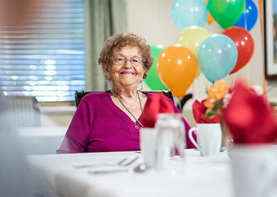 Brookdale resident at her birthday party with balloons in the background.