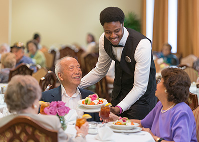 Dining server greets senior guests
