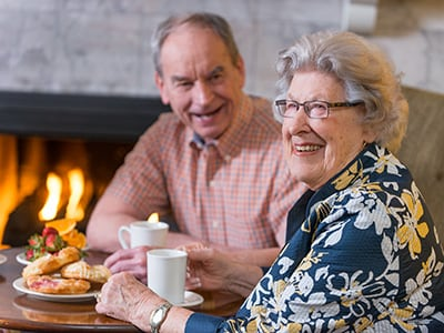 couple eating breakfast next to fireplace