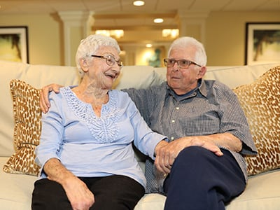 elderly couple holding hands on a couch