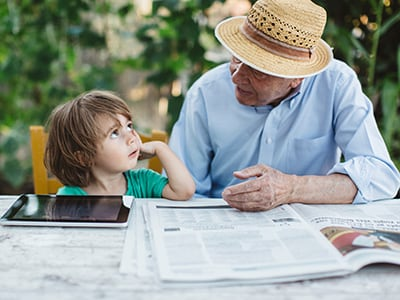 grandfather and grandson reading the newspaper