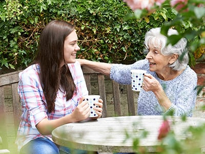 grandmother and granddaughter sitting outside drinking tea