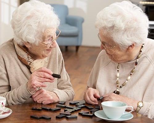 two woman playing dominos