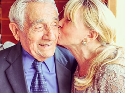daughter kissing elderly father