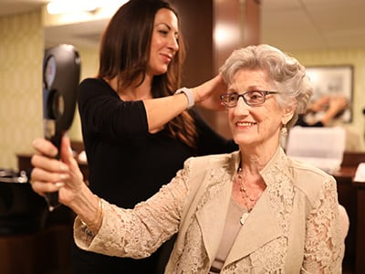 older woman looking in mirror with hairdresser