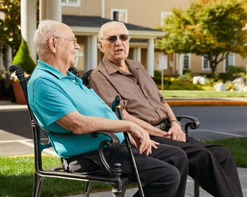 men talking on bench