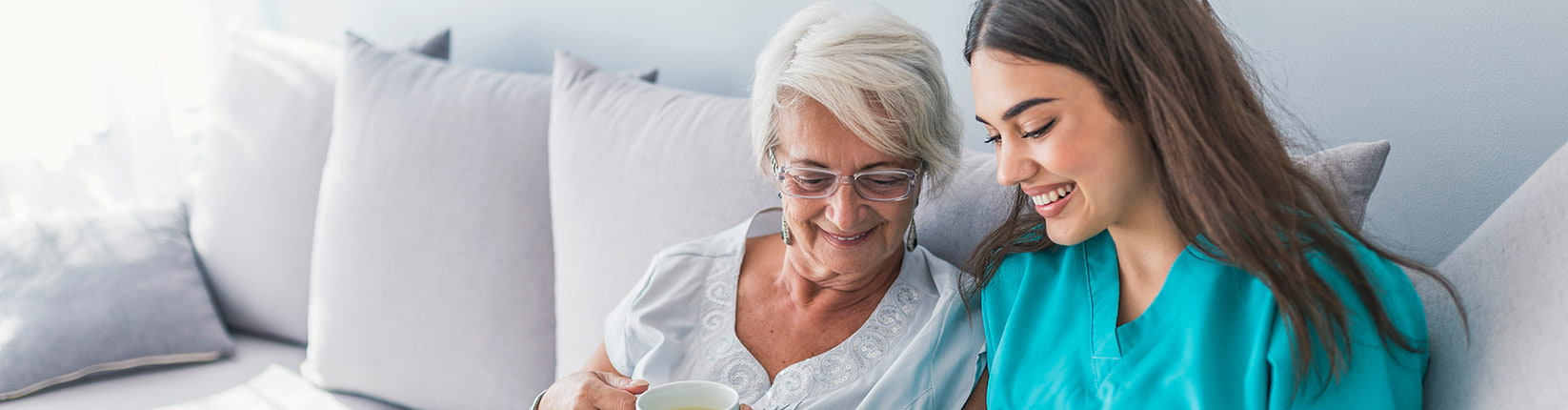woman drinking tea with caregiver