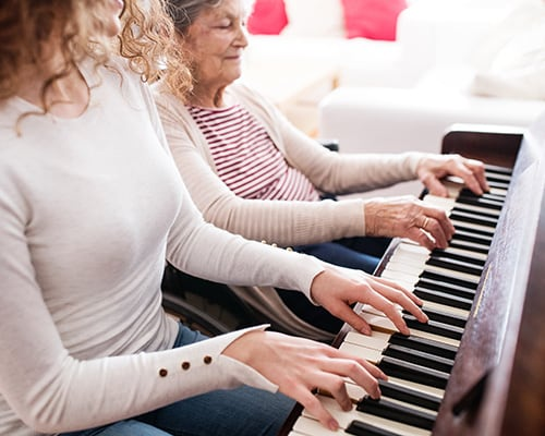 woman with caregiver playing piano