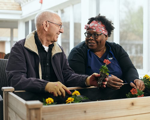man gardening with caregiver
