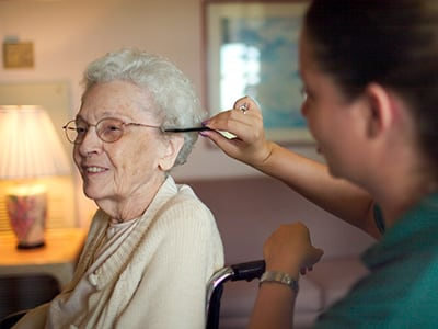 caregiver combing woman's hair