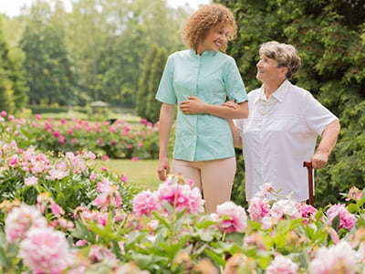 caregiver walking with woman in the garden