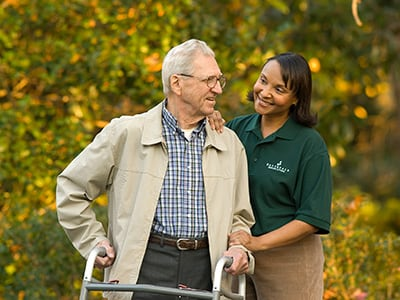 man with walker walking with caregiver