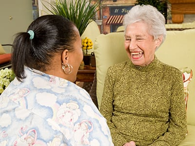 woman and caregiver laughing