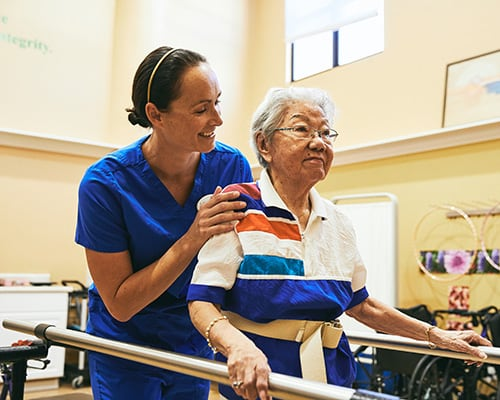 caregiver and woman on support bars