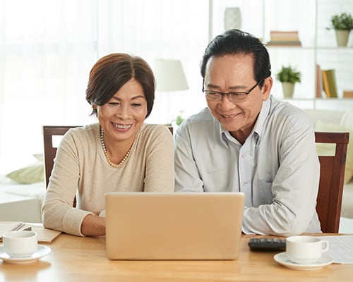 couple smiling with tea and computer