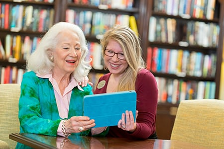 associate helping senior woman with iPad